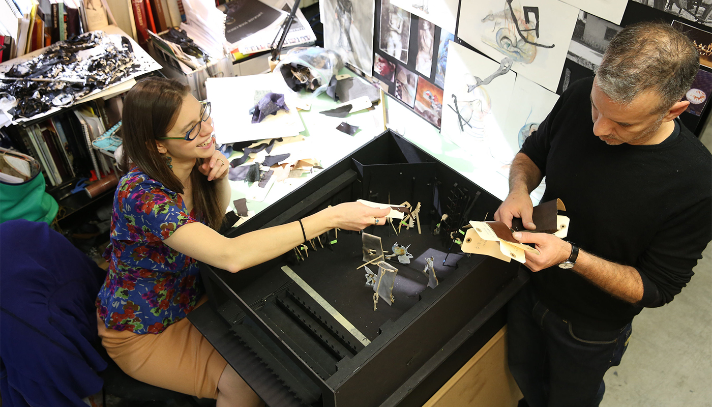 two people at a desk with miniature set and costume images, designs