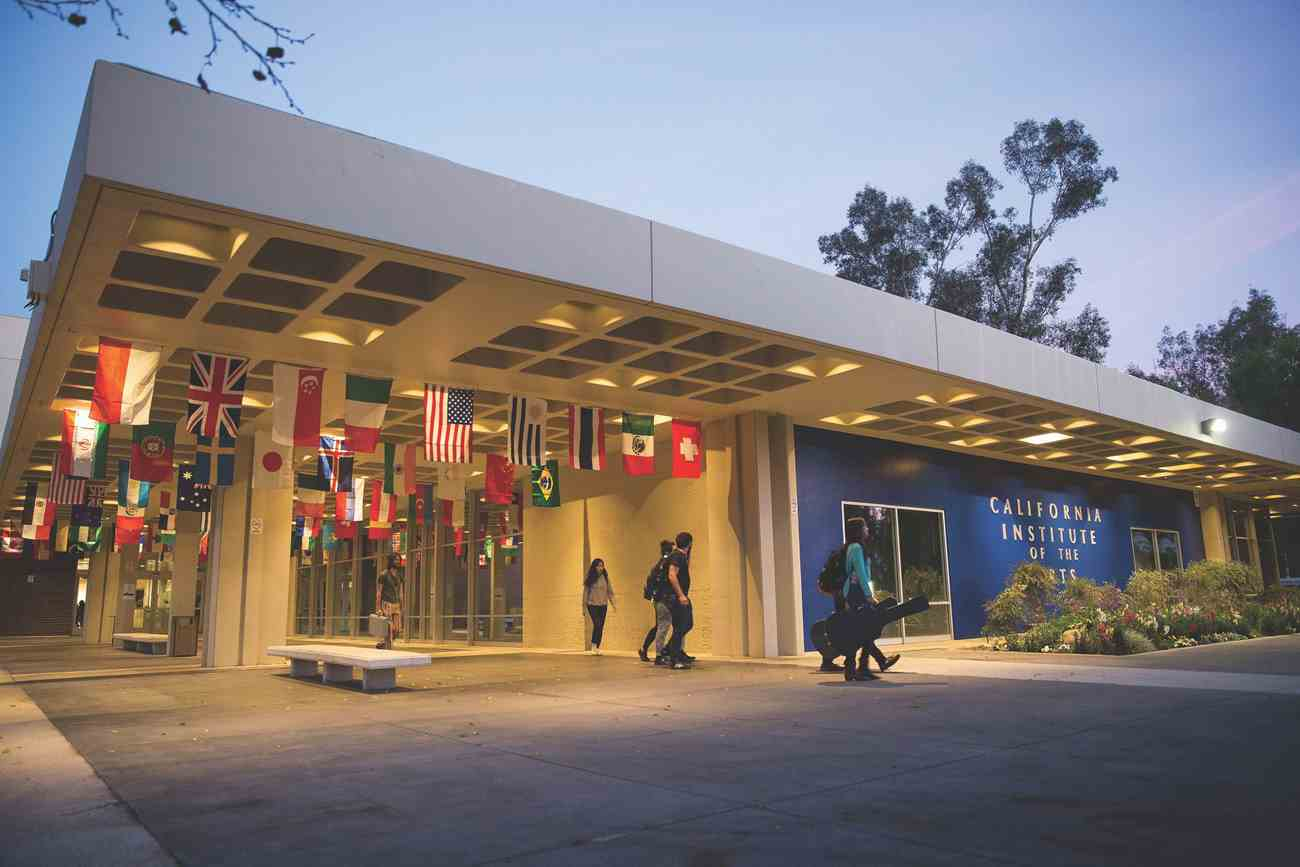 the blue wall entryway of calarts with flags