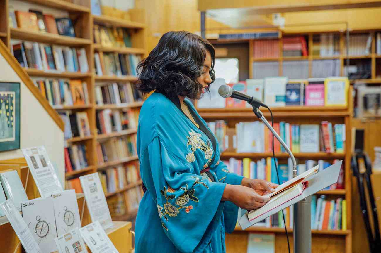 a woman reading at a podium at a bookstore