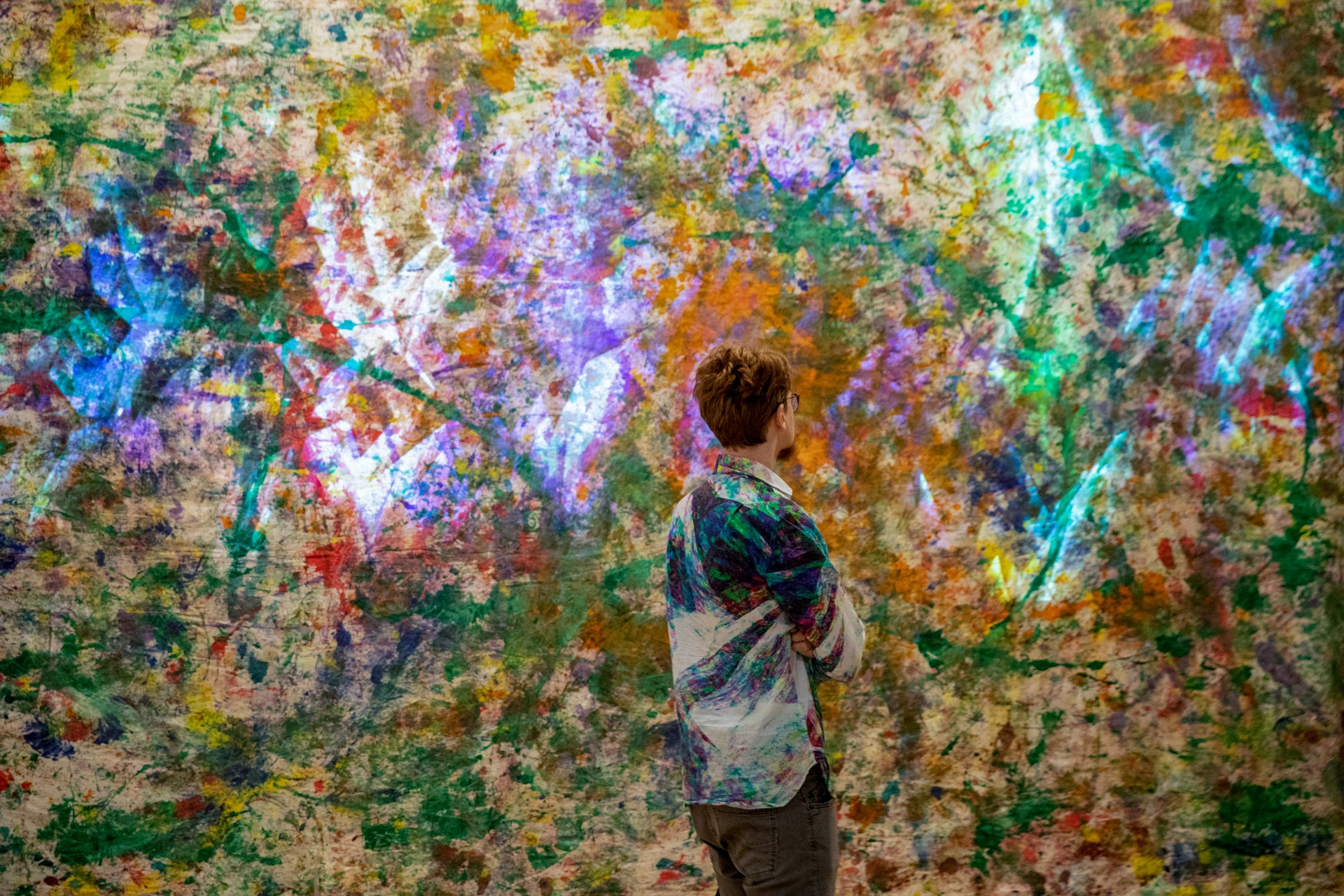 a student looking at colorful art on a wall, which matches his shirt