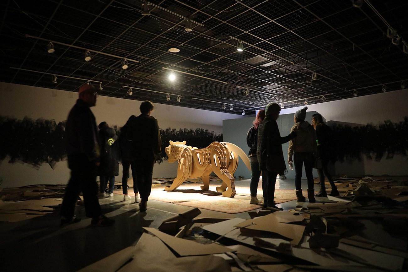 During a gallery opening, people crowded around an actual sized 3d wooden sculpture of a tiger