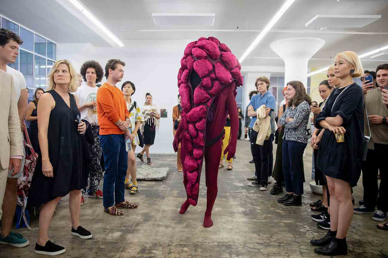 Performance piece of a person in a pink nebulous costume in the middle of a crowd