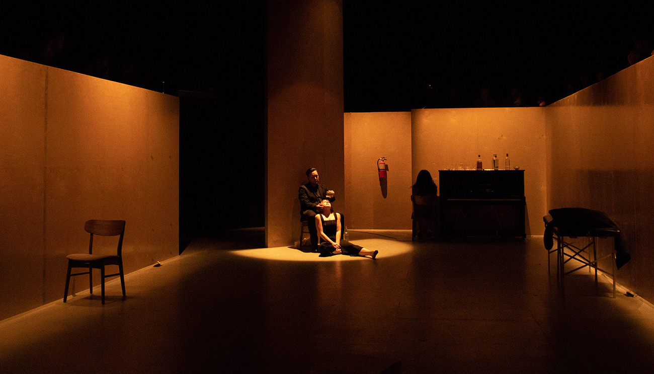 Two actors sit in a darkened room during performance